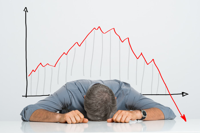 Depressed Businessman Leaning His Head Below a Bad Stock Market