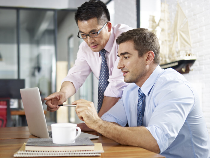 asian and caucasian businessmen working together in office learn