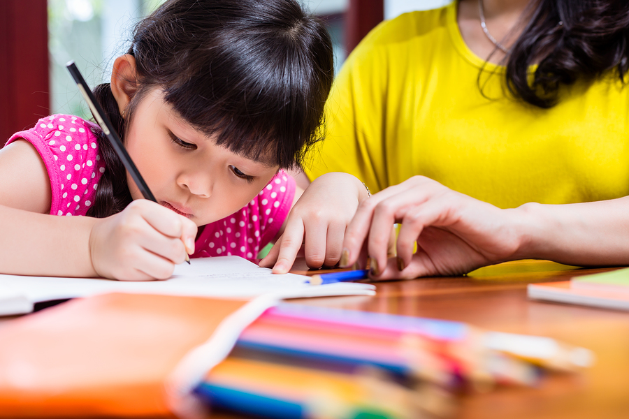 Chinese mother homeschooling her child teaching her daughter to