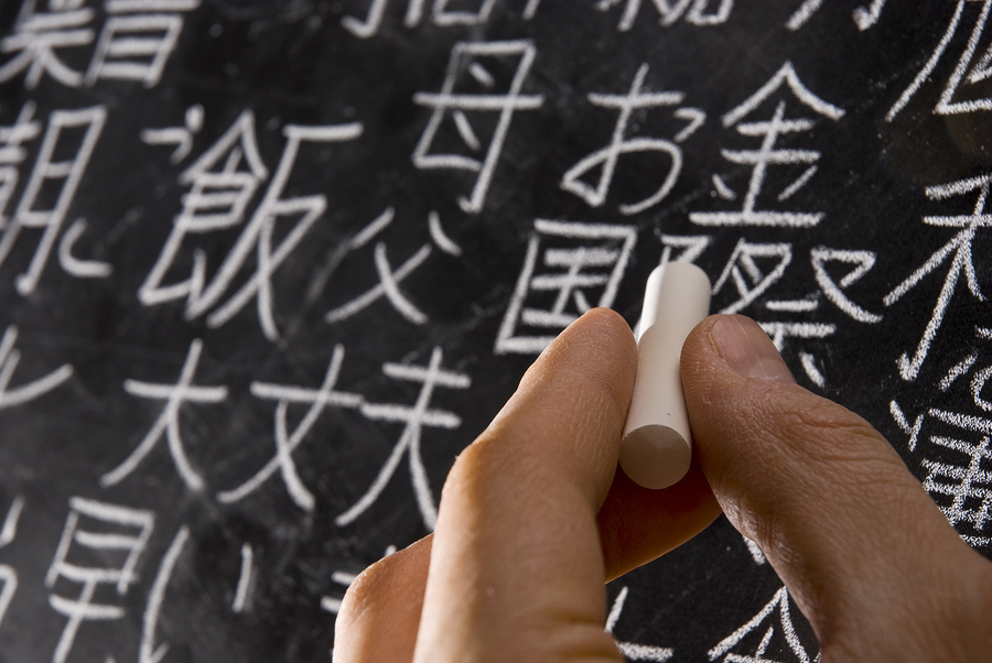 Close up of male hand writing Chinese and Japanese characters on
